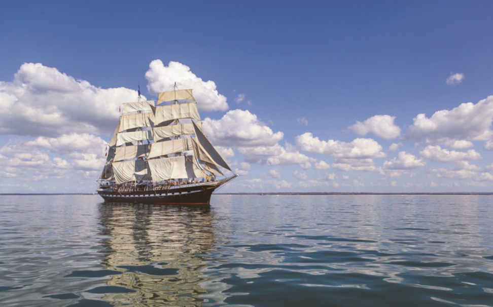 A scenic view of huge ship with numerous white raised sails swims along the blue water - Marshalls